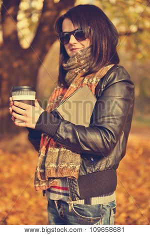 Female Holding Cup Of Coffee And Book