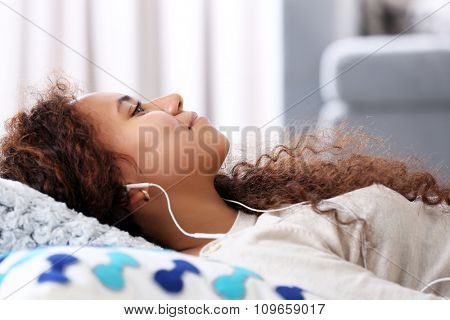 Close up portrait of listening music pretty girl who resting on  the floor
