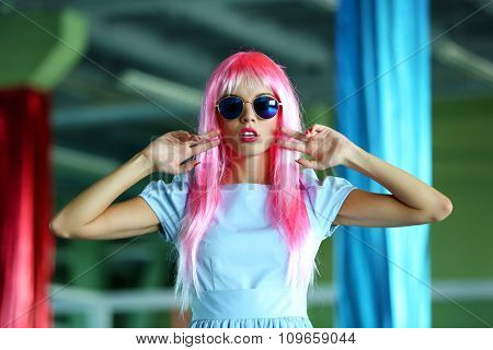 Young woman in dress posing like doll inside empty building