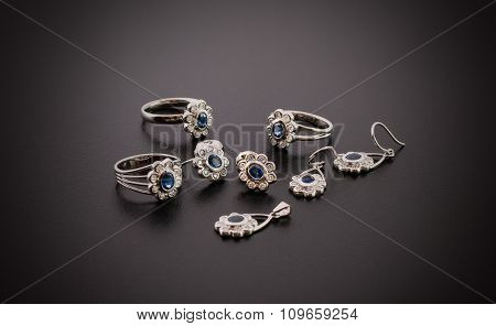 Gold rings, earrings and pendant with diamonds and sapphires on black background