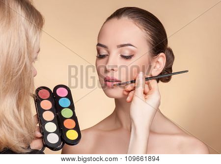Skillful young visagiste is working at beauty salon