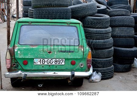 Old green Azerbaijani car in Baku, under a pile and full of tyres, from behind