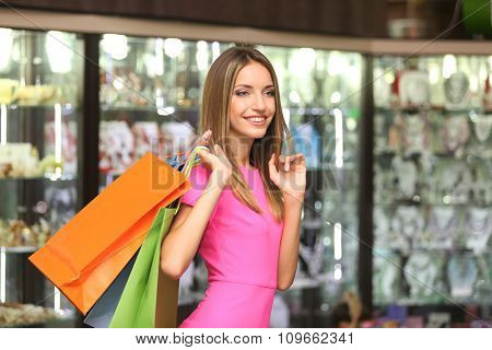 Beautiful young woman with shopping bags in shop