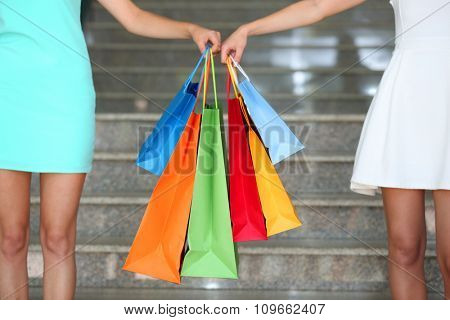 Beautiful young women with shopping bags on steps