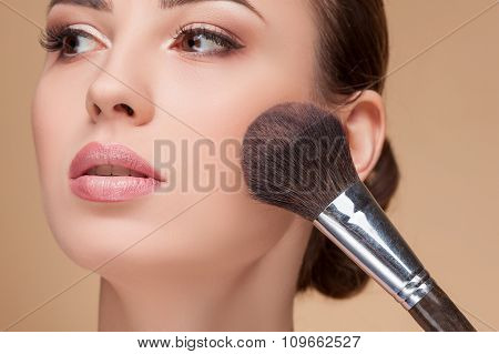 Attractive young woman is getting make-up at salon