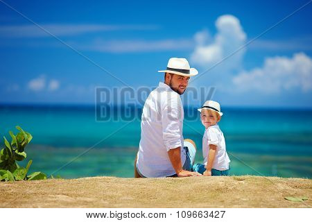 Happy Father And Son Sitting Near The Sea During Summer Vacation