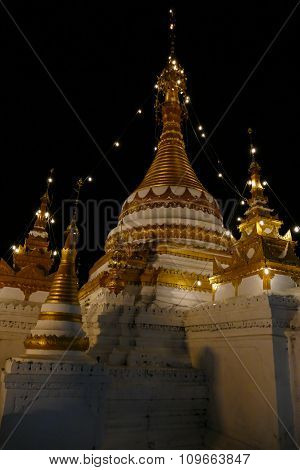 White And Golden Buddhist Pagoda Monument At Night