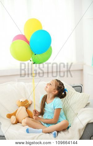 Beautiful little girl with teddy bear and colorful balloons sitting on sofa, on home interior background