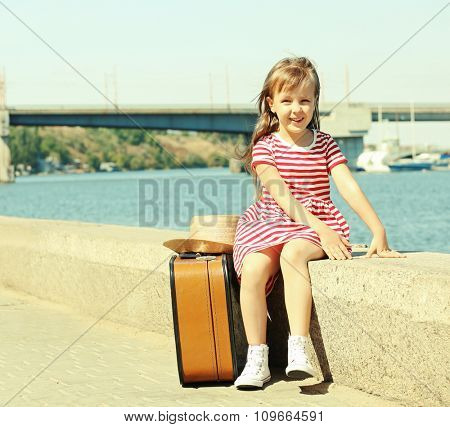 Little girl with suitcase on the riverside