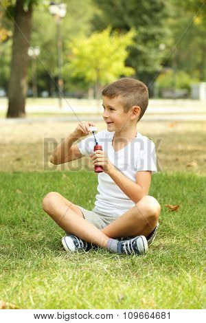 Little boy playing with bubbles in the park