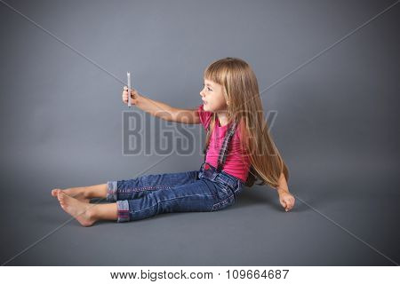 Beautiful little girl with mobile phone, on grey background