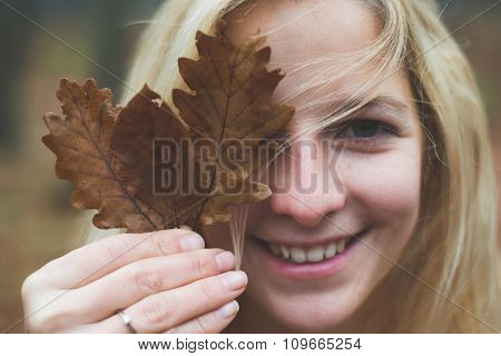 Smiling blonde woman holding leaves in front of her eye and looking at camera. Outdoor in the forest.
