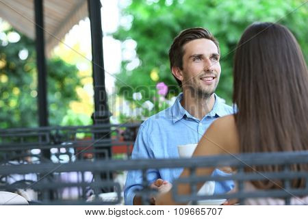 Young man and woman in street cafe