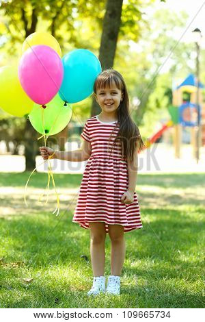Little girl with balloons in the park