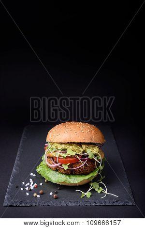 Turkey burger with pesto sauce on black stone board.