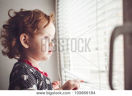 Little Girl Looking Out The Window Through The Blinds