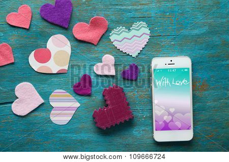 White smart phone with hearts on wooden desk.