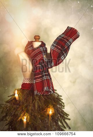 Vintage tailors dummy dressed for winter with tartan scarf and festive Christmas candles