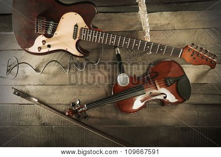 Electric guitar, violin, flute and microphone on wooden background