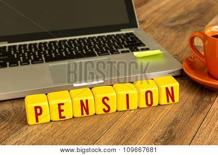 Pension written on a wooden cube in a office desk