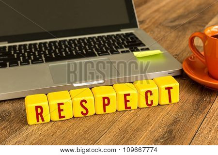 Respect written on a wooden cube in a office desk