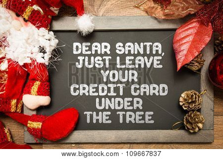 Blackboard with the text: Dear Santa, Just Leave Your Credit Card Under the Tree