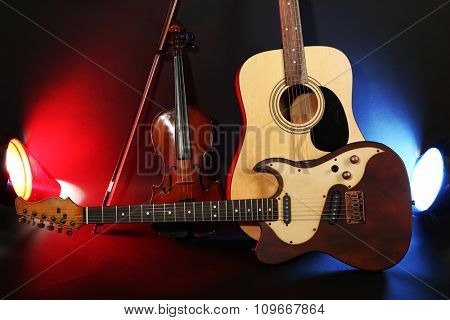 Electric and acoustic guitars, violin on dark background