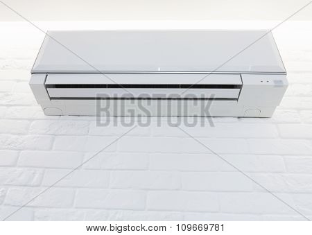 White Air Conditioner Mounted On The Brick Painted Wall
