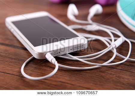 White cellphone with headphones and pink dumb bells and gumshoes on varnished wooden background, close up