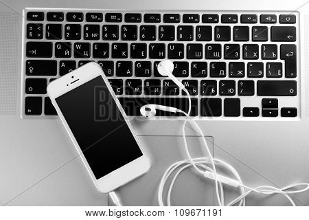 White cellphone with headphones on laptop, close up