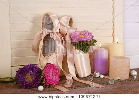 Decorated with flowers and candles ballet shoes on creamy wooden background