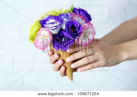 Woman's hand holding wild flowers in wafer on light wall background