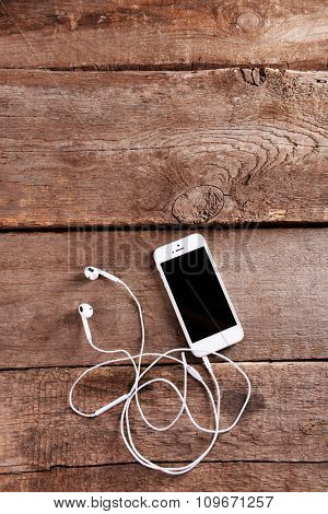White cellphone with headphones on wooden background