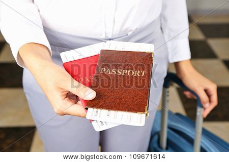 Woman with suitcase holding passports and tickets close up