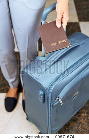 Woman with suitcase holding passport close up