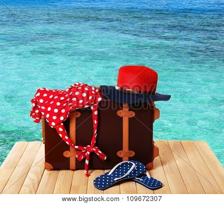 Suitcase with beach accessories on wooden board on sea background
