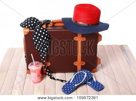 Suitcase with beach accessories on wooden board on white background