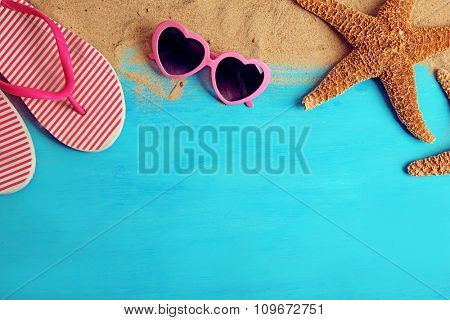 Starfish, sunglasses and flip flops with sand on wooden background