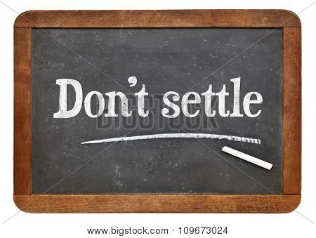 Do not settle - motivational advice in white chalk on a vintage slate blackboard