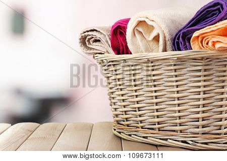 Colorful towels in basket on bright background