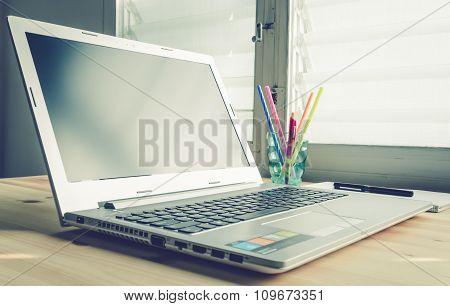 Laptop And Notebook And Pen On Wood Table On Blue Vintage Style