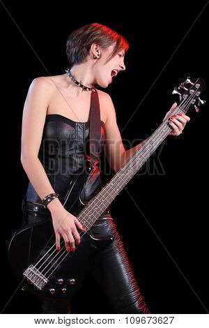 Sexy girl in leather clothes with bass guitar. punk rocker