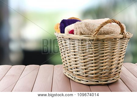 Colorful towels in basket on blurred background