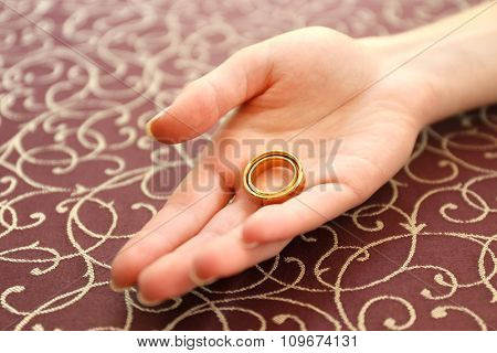 Female hand with wedding rings over tablecloth background