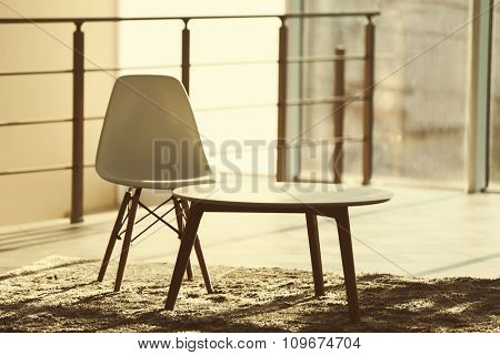 White modern chair and a table in lighted room, on window background