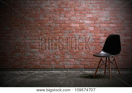 Black modern chair on red brick wall background