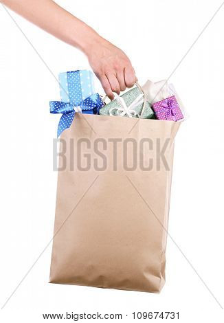 Female hand holding paper bag with present boxes isolated on white