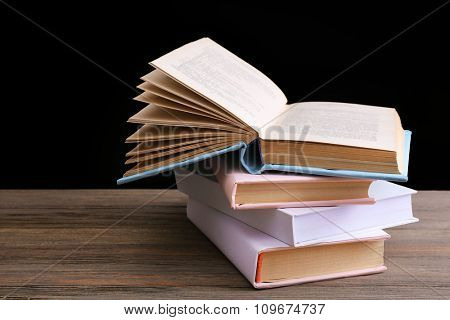 Pile of different books on wooden table against black background
