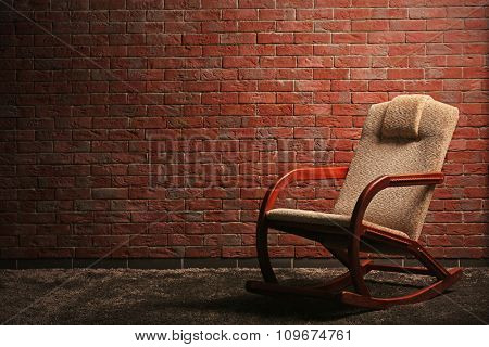 Comfortable rocking chair on red brick wall background