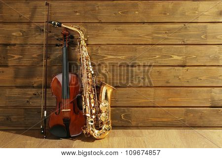Violin and saxophone on wooden background